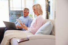 Pares maduros en casa en salón usando los dispositivos de Digitaces imagenes de archivo