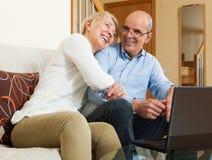 Pares maduros felices con el ordenador portátil Foto de archivo libre de regalías
