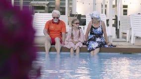 Pares maduros felices de la diversión con poca nieta que se sienta al borde de la piscina de lujo Abuela, abuelo y almacen de metraje de vídeo