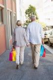Pares maduros felices que caminan con sus compras de las compras Foto de archivo