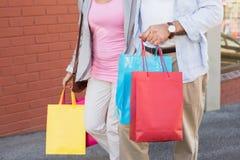 Pares maduros felices que caminan con sus compras de las compras Fotografía de archivo