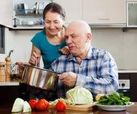 Pares maduros felices que cocinan junto Imagen de archivo