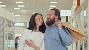Pares maduros felices que disfrutan de venta estacional en el centro comercial local metrajes
