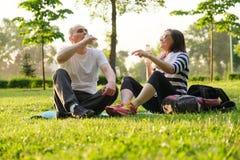 Pares maduros felices que se sientan en el parque en la estera de la aptitud, yogur de consumición de reclinación después de ejer foto de archivo libre de regalías