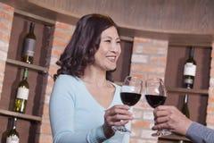 Pares maduros felices sonrientes en una degustación de vinos, tostando Imagenes de archivo