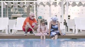 Pares maduros felizes e sua neta pequena que sentam-se na borda da associação Avó, avô, e video estoque