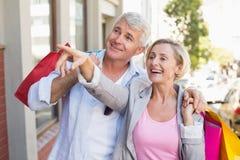 Pares maduros felizes que andam com suas compras da compra Foto de Stock Royalty Free