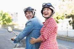 Pares maduros felizes que montam um 'trotinette' na cidade Fotos de Stock Royalty Free