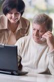 Pares maduros felizes que trabalham no portátil Fotos de Stock Royalty Free