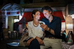 Pares maduros felizes usando o smartphone na noite foto de stock royalty free