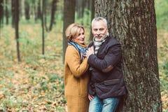 Pares maduros hermosos en parque del otoño Imágenes de archivo libres de regalías