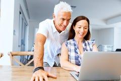 Pares maduros modernos felizes que trabalham no portátil em casa imagens de stock royalty free