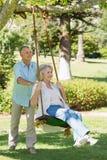 Pares maduros no balanço no parque imagens de stock royalty free
