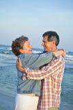 Pares maduros que abraçam na praia Fotografia de Stock