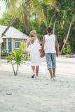 Pares maduros que abrazan caminar en la playa Fotos de archivo