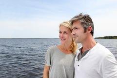 Pares maduros que abrazan por el lago Foto de archivo libre de regalías
