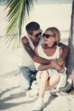 Pares maduros que abrazan sentarse en la playa Imagen de archivo libre de regalías
