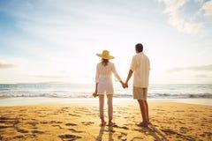 Pares maduros que andam na praia no por do sol fotografia de stock