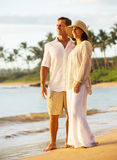 Pares maduros que apreciam o por do sol na praia imagens de stock royalty free