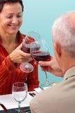 Pares maduros que brindam com vinho vermelho imagem de stock royalty free