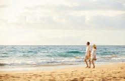 Pares maduros que caminan en la playa en la puesta del sol foto de archivo