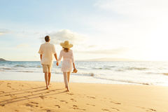 Pares maduros que caminan en la playa en la puesta del sol imagenes de archivo