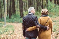Pares maduros que caminan en parque del otoño Imagenes de archivo