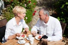 Pares maduros que comen café en el pórtico Fotos de archivo