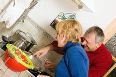 Pares maduros que cozinham pratos na cozinha foto de stock royalty free