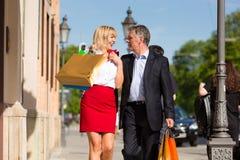 Pares maduros que dan un paseo con compras de la ciudad Fotografía de archivo