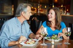 Pares maduros que disfrutan de la comida en el restaurante al aire libre Fotografía de archivo