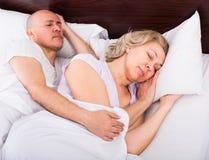 Pares maduros que dormem na cama Fotografia de Stock