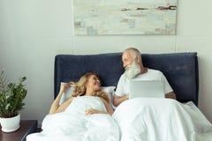 Pares maduros que encontram-se junto na cama com portátil e que sorriem-se Fotos de Stock Royalty Free