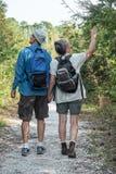 Pares maduros que guardam as mãos e que caminham na natureza t Fotografia de Stock Royalty Free
