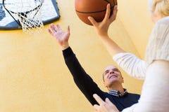 Pares maduros que jogam o basquetebol no pátio Imagem de Stock Royalty Free