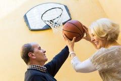 Pares maduros que jogam o basquetebol no pátio Fotografia de Stock