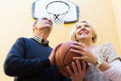 Pares maduros que jogam o basquetebol no pátio Imagens de Stock Royalty Free