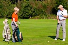 Pares maduros que jogam o golfe fotografia de stock