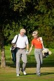 Pares maduros que juegan a golf Foto de archivo