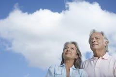 Pares maduros que olham acima contra o céu Imagem de Stock
