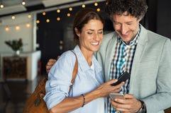 Pares maduros que olham o smartphone imagens de stock