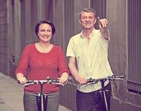 Pares maduros que permanecen con las bicis eléctricas imagenes de archivo