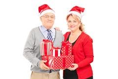 Pares maduros que presentan con los regalos de Navidad Fotografía de archivo libre de regalías