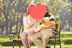 Pares maduros que se besan detrás de un corazón rojo en un parque Imágenes de archivo libres de regalías