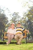 Pares maduros que se sientan en banco en un parque Imagenes de archivo