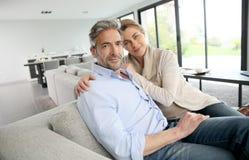 Pares maduros que sentam em casa o relaxamento foto de stock
