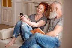 Pares maduros que sentam-se junto no sofá e que usam o smartphone e a tabuleta digital fotos de stock
