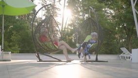 Pares maduros que sentam-se na cadeira de suspensão no por do sol, relaxando no complexo do hotel junto A tabuleta da terra arren video estoque
