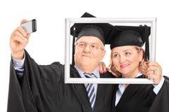 Pares maduros que toman un selfie detrás de marco Foto de archivo