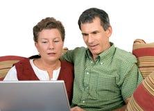 Pares maduros que trabajan en la computadora portátil junto Fotos de archivo libres de regalías